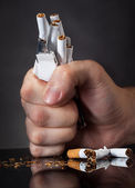 Man's Fist Crushing Cigarettes — Stock Photo
