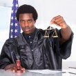 Stock Photo: Male Judge Holding Gavel And Scale In Courtroom