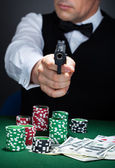 Portrait of a croupier aiming with a gun — Stock Photo