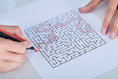 Close-up Of Hand Solving Maze Puzzle — Stock Photo