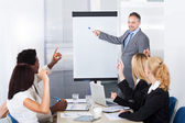 Businesspeople Looking At Man Explaining — Stock Photo