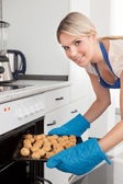 Woman Placing Cookies In Oven — Stock Photo