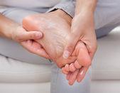 Woman applying cream on feet — Stock Photo