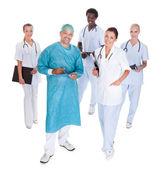 Glad läkare i kirurgiska klänning med hans medarbetare — Stockfoto