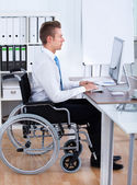 Businessman Sitting On Wheelchair And Using Computer — Stock Photo