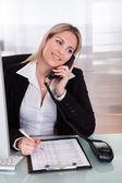 Happy businesswoman talking on telephone — Stock Photo