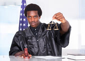 Male Judge Holding Gavel And Scale In Courtroom — Stock Photo