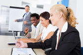 Business executives taking notes during a meeting — Stock Photo