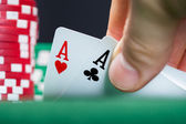 Poker player lifting the corners of two cards — Stock Photo
