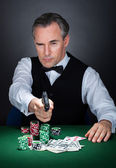 Portrait of a croupier aiming with a gun — Stok fotoğraf