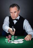Porträtt av en croupier sikte med en pistol — Stockfoto
