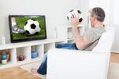 Mature man watching football on television — Stock Photo