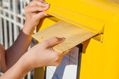 Woman inserting envelope in mailbox — Stock Photo
