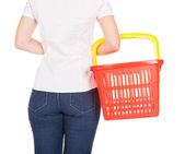 Woman holding empty shopping basket — Stock Photo