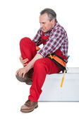 Male Technician suffering from knee pain — Stock Photo