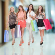 Four happy women returning from shopping — Stockfoto