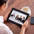 Stock Photo: WomVideo Conferencing On Digital Table