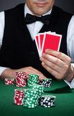 Krupiér drží hrací karty — Stock fotografie
