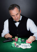 Portret van een croupier kijken speelkaarten — Stockfoto