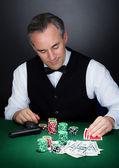 Porträtt av en croupier tittar på spelkort — Stockfoto