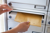 Woman putting envelope in mailbox — Stock Photo