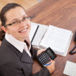 Happy young woman calculating finances — Stock Photo