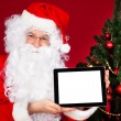 Portrait of a happy santa holding digital tablet — Stock Photo