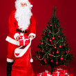 Portrait of a santa holding gift — Stockfoto