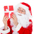 Portrait of a happy santa holding gift — Stock Photo