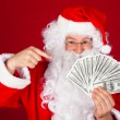 Happy santa holding dollars — Stock Photo