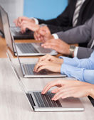 Close-up Of Businesspeople Using Laptop — Stock Photo