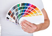 Young man holding color palette — Stock Photo
