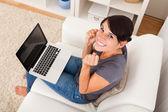 Ung kvinna sitter med laptop — Stockfoto