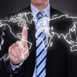 Stock Photo: Businessmtouching world map on screen