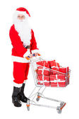 Portrait of santa holding shopping cart — Stock Photo