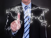Businessman touching world map on the screen — Stock Photo