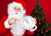 Portrait of a happy santa holding clock — Stock Photo