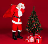 Santa carrying gifts in sack — Stock Photo