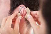 Person Adjusting Hearing Aid — Stock Photo