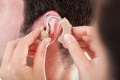 Person Adjusting Hearing Aid — Stockfoto