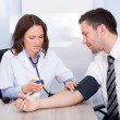 Young Doctor Checking Blood Pressure — Stock Photo #35620835