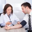 Stock Photo: Young Doctor Checking Blood Pressure