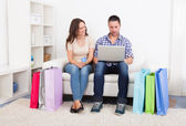 Young Couple Sitting On Couch Shopping Online — Foto de Stock