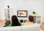 Young family watching TV — Stock Photo