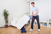 Young Man With Box On Trolley — Stock Photo