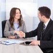Stock Photo: Looking At BusinessmWhile Shaking Hand At Office Desk