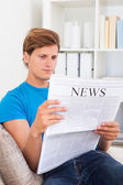 Man Sitting On Sofa And Reading Newspaper — Stock Photo