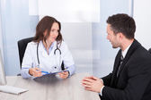 Female Doctor Looking At Businessman — Stockfoto