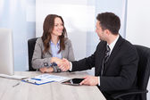 Looking At Businessman While Shaking Hand At Office Desk — Stock Photo