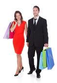 Pareja joven sosteniendo bolsas de compras — Foto de Stock